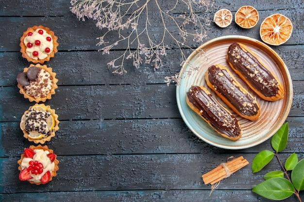 Bovenaanzicht chocolade eclairs op ovale plaat gedroogde bloemtak kaneel gedroogde sinaasappels bladeren en verticale rij taarten op de donkere houten tafel met kopie ruimte Gratis Foto