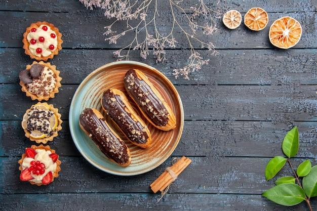 Bovenaanzicht chocolade eclairs op ovale plaat gedroogde bloemtak kaneel gedroogde sinaasappels bladeren en verticale rij taarten op de donkere houten tafel met vrije ruimte
