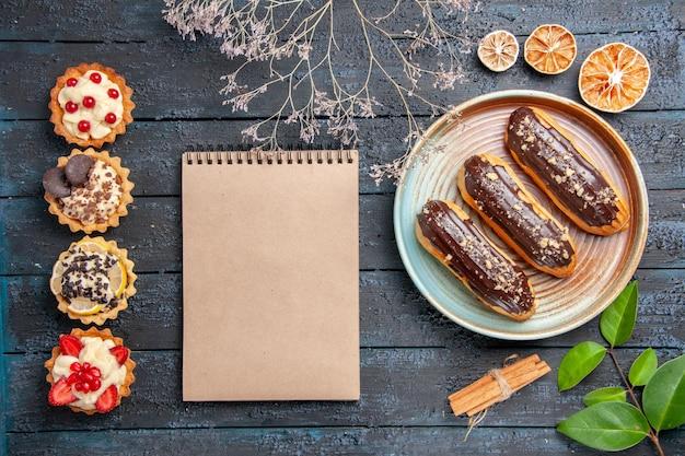 Bovenaanzicht chocolade eclairs op ovale plaat gedroogde bloemtak kaneel gedroogde sinaasappels laat een notitieboekje en verticale rij taarten op de donkere houten tafel