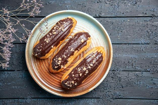 Bovenaanzicht chocolade eclairs op ovale plaat gedroogde bloemtak op de donkere houten tafel met vrije ruimte