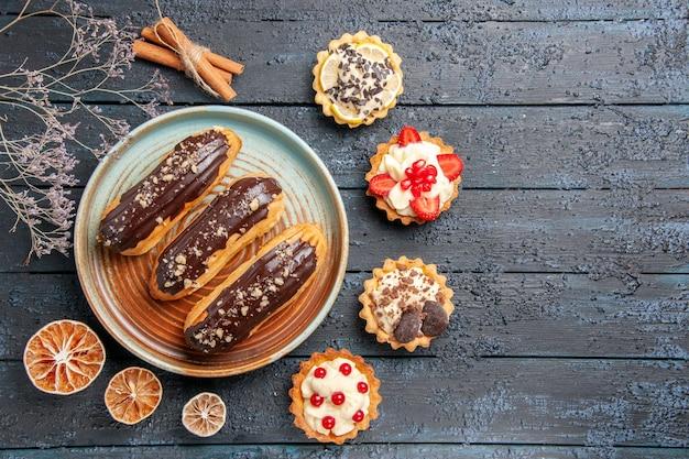 Bovenaanzicht chocolade-eclairs op ovale plaat omringd met gedroogde citroenen en taartjes aan de linkerkant van de donkere houten tafel met kopie ruimte