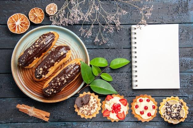 Bovenaanzicht chocolade eclairs op ovale plaat taarten laeves kaneel gedroogde sinaasappels en een notitieboekje op de donkere houten tafel