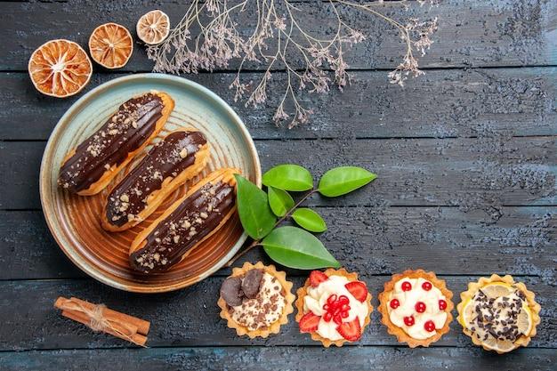Bovenaanzicht chocolade eclairs op ovale plaat taarten laeves kaneel gedroogde sinaasappels en op de donkere houten tafel met kopie ruimte