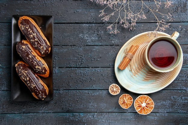 Bovenaanzicht chocolade-eclairs op rechthoekige plaat aan de linkerkant en een kopje thee, gedroogde citroenen en kaneel aan de rechterkant op de donkere houten tafel met vrije ruimte