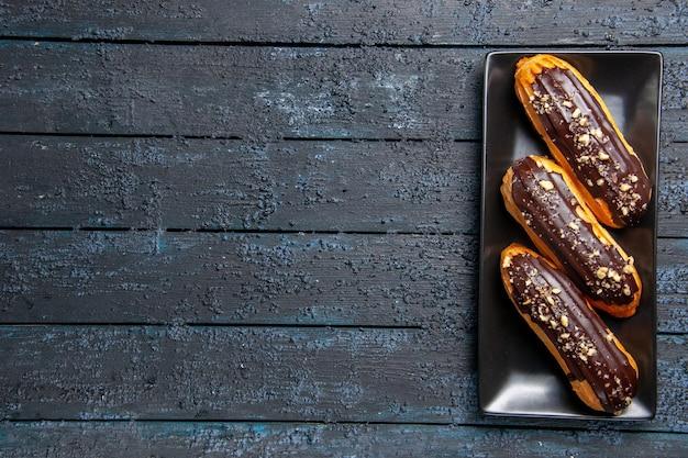 Bovenaanzicht chocolade-eclairs op rechthoekige plaat aan de rechterkant van de donkere houten tafel met vrije ruimte Gratis Foto