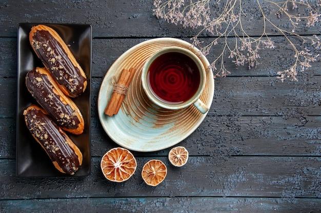 Bovenaanzicht chocolade-eclairs op rechthoekige plaat en een kopje thee, gedroogde citroenen en kaneel op de donkere houten tafel met vrije ruimte