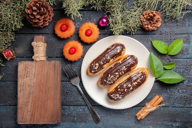 Bovenaanzicht chocolade eclairs op witte ovale plaat fir-tree takken en kegels kerst speelgoed een vork kaneel een kopje thee en een snijplank op donkere houten tafel
