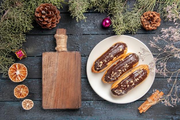 Bovenaanzicht chocolade eclairs op witte ovale plaat fir-tree takken en kegels kerst speelgoed gedroogde bloemtak gedroogde sinaasappels kaneel en snijplank op donkere houten tafel