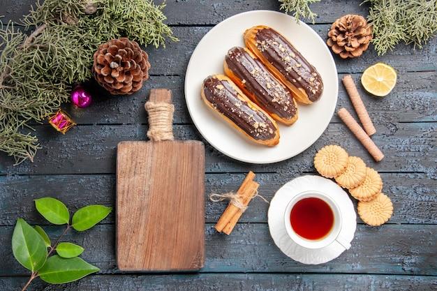 Bovenaanzicht chocolade eclairs op witte ovale plaat kegels dennenboom bladeren kaneel schijfje citroen verschillende koekjes een kopje thee en een snijplank op donkere houten grond