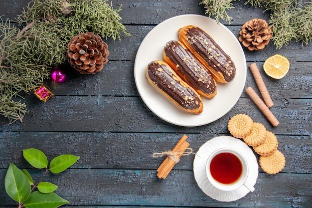 Bovenaanzicht chocolade eclairs op witte ovale plaat kegels dennenboom bladeren kaneel schijfje citroen verschillende koekjes en een kopje thee op donkere houten ondergrond met kopie ruimte