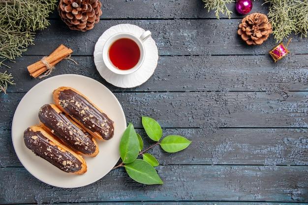 Bovenaanzicht chocolade eclairs op witte ovale plaat kegels kerst speelgoed dennenboom bladeren kaneel en een kopje thee op donkere houten grond met kopie ruimte