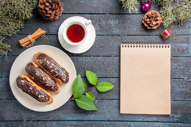 Bovenaanzicht chocolade eclairs op witte ovale plaat kegels kerst speelgoed dennenboom bladeren kaneel en een notitieboekje op donkere houten grond