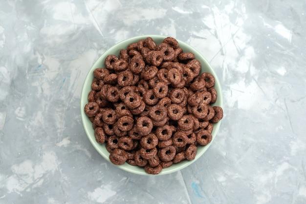 Bovenaanzicht chocolade granen in groene plaat op blauw, cacao ontbijt granen gezondheid van het voedsel