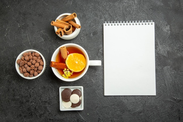 Bovenaanzicht chocolade hazelnoten wit notitieboekje en kommen kaneelstokjes chocolade en hazelnoten naast het kopje thee met kaneel en citroen aan de linkerkant van de tafel
