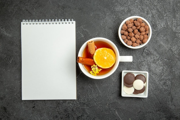 Bovenaanzicht chocolade hazelnoten wit notitieboekje naast de kommen chocolade en hazelnoten en kopje thee met kaneel en citroen op het donkere oppervlak