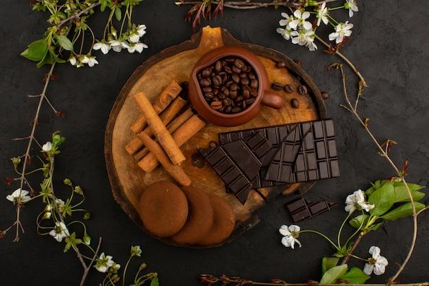 Bovenaanzicht chocolade kaneel koffie op het bruine houten bureau en donker