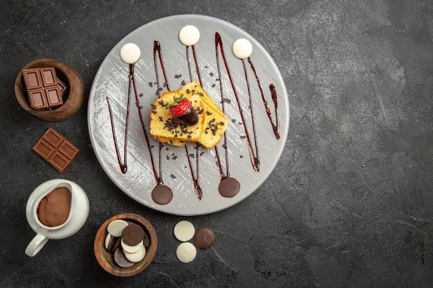 Bovenaanzicht chocolade op de tafelplaat van cake met met chocolade omhulde aardbeien en chocolade en chocoladeroom in de houten kommen op de zwarte tafel