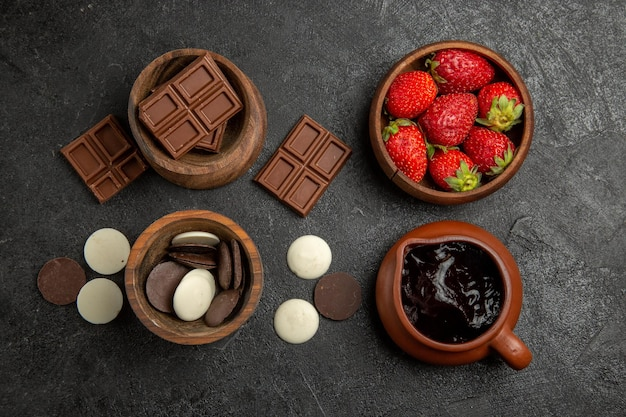 Bovenaanzicht chocolade op tafel bruine kommen chocolade aardbeien en chocoladesaus op het donkere oppervlak