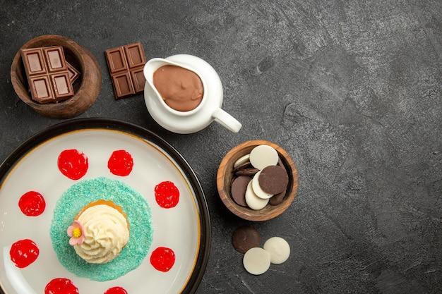 Bovenaanzicht chocolade op tafel cupcake met room en sauzen naast de kommen chocolade en chocoladeroom op de donkere tafel