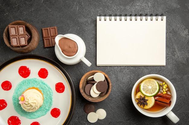 Bovenaanzicht chocolade op tafel cupcake met room en sauzen naast het kopje kruidenthee en witte notebookkommen chocolade en chocoladeroom op de donkere tafel