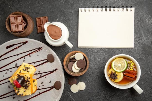 Bovenaanzicht chocolade op tafel taart met aardbeien en chocolade naast het kopje kruidenthee en witte notebook kommen chocolade op de donkere tafel