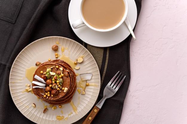 Bovenaanzicht chocolade pannenkoeken met hazelnoten, kiwi, kokosvlokken en ahornsiroop in beige plaat met witte kop koffie op keukenschort op roze achtergrond