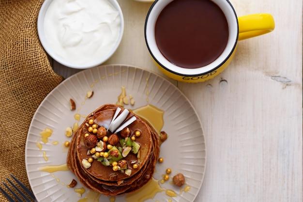 Bovenaanzicht chocolade pannenkoeken met kiwi, hazelnoot, honing op plaat met zure room en kopje cacao op witte achtergrond
