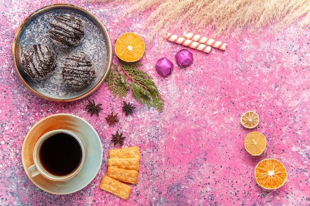 Bovenaanzicht chocoladecake met kopje thee op roze bureau