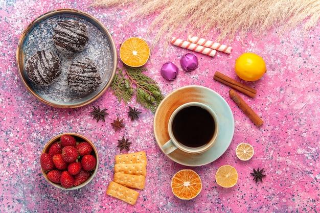 Bovenaanzicht chocoladecake met kopje thee op roze