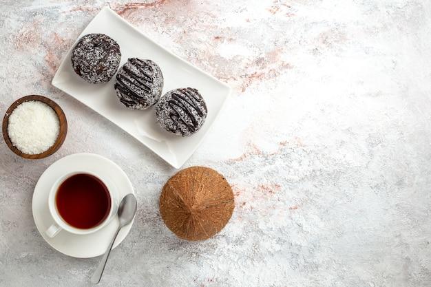Bovenaanzicht chocoladecake met kopje thee op witte achtergrond chocoladetaart koekje suiker zoete koekjes