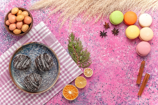 Bovenaanzicht chocoladecake met macarons op roze bureau
