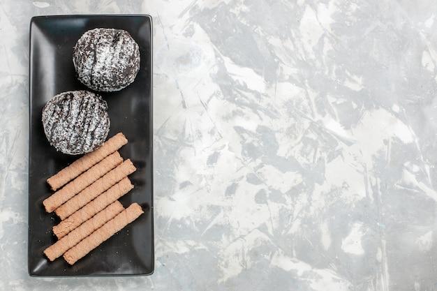 Bovenaanzicht chocoladecake met zoete pijpkoekjes binnen zwarte plaat op wit bureau