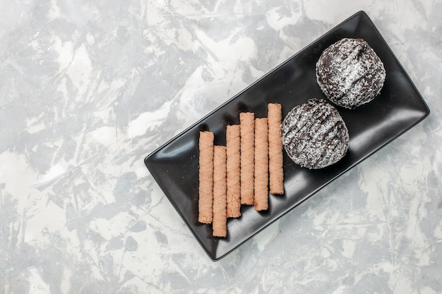 Bovenaanzicht chocoladecake met zoete pijpkoekjes in zwarte plaat op wit oppervlak
