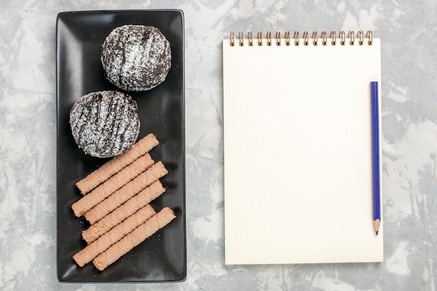 Bovenaanzicht chocoladecake met zoete pijpkoekjes op witte ondergrond