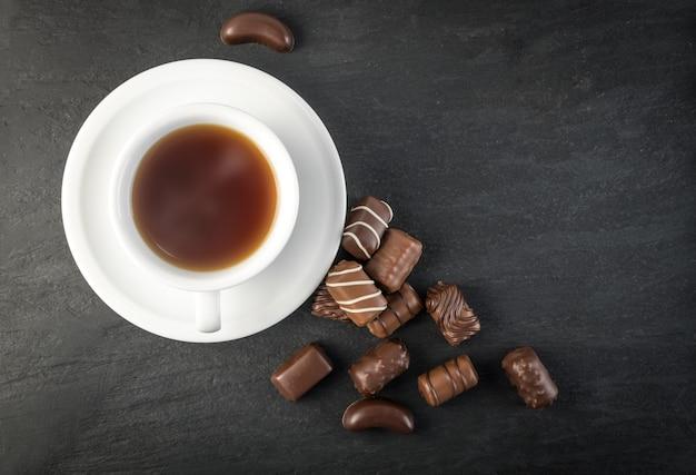 Bovenaanzicht chocoladesnoepjes en koffiekopje mockup