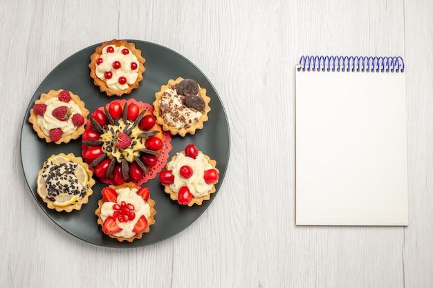 Bovenaanzicht chocoladetaart afgerond met bessentaartjes in de grijze plaat en een notitieboekje op de witte houten tafel