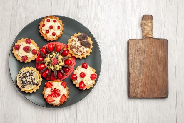 Bovenaanzicht chocoladetaart afgerond met bessentaartjes in de grijze plaat en een snijplank op de witte houten tafel