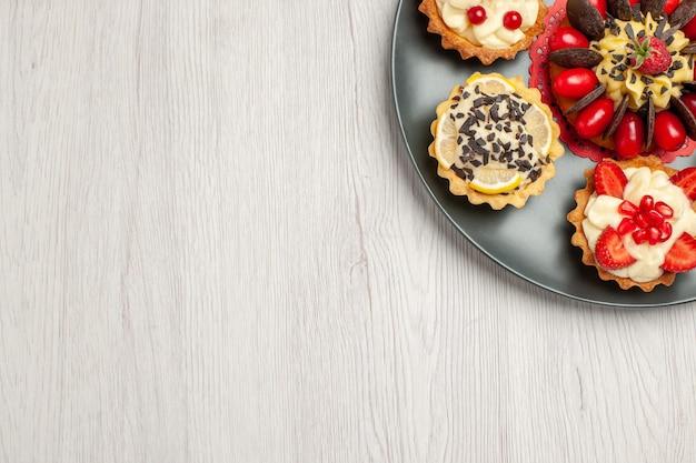 Bovenaanzicht chocoladetaart afgerond met bessentaartjes in de grijze plaat rechtsboven op de witte houten tafel