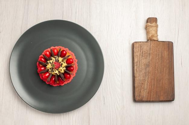 Bovenaanzicht chocoladetaart afgerond met cornel en framboos in het midden in de grijze plaat en een snijplank op de witte houten achtergrond