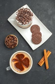 Bovenaanzicht chocoladetaart en koekjes op witte rechthoekige plaat kopje koffie kaneelstokjes kom met koffiezaden op donkere geïsoleerde achtergrond