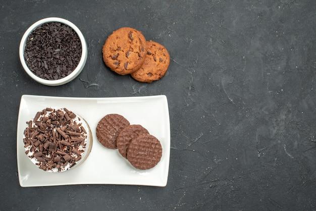 Bovenaanzicht chocoladetaart en koekjes op witte rechthoekige plaatkom met chocoladekoekjes op donkere geïsoleerde achtergrond