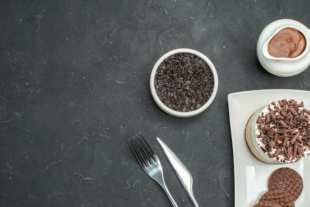 Bovenaanzicht chocoladetaart en koekjes op witte rechthoekige plaatkom met chocoladevork en mes op donkere geïsoleerde achtergrond