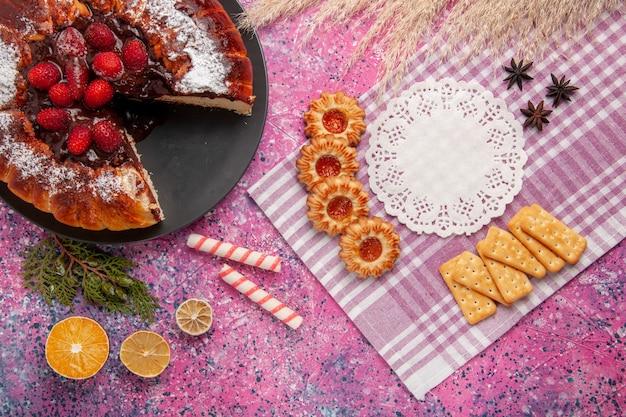 Bovenaanzicht chocoladetaart met aardbeiencrackers en koekjes op het roze zoete koekje van de bureausuiker Gratis Foto