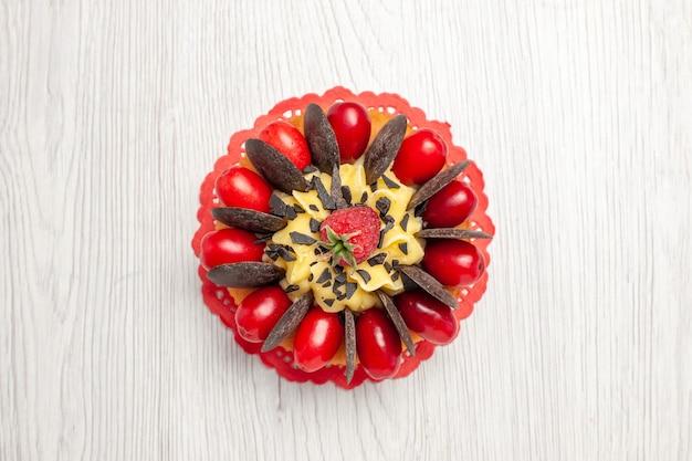 Bovenaanzicht chocoladetaart met bessen op het rode ovale kanten kleedje op de witte houten tafel