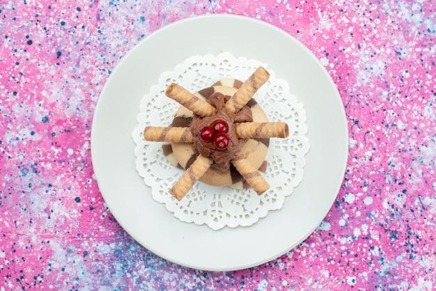 Bovenaanzicht chocoladetaart met koekjes in witte plaat op de paarse achtergrond cookie koekje suiker zoet
