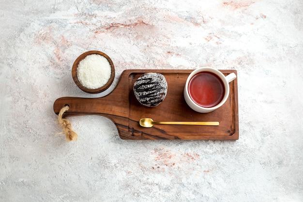 Bovenaanzicht chocoladetaart met kopje thee op de witte achtergrond chocoladetaart koekje suiker zoet koekje
