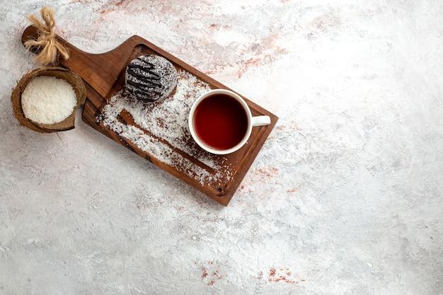 Bovenaanzicht chocoladetaart met kopje thee op witte achtergrond chocoladetaart koekje suiker zoete koekjesthee