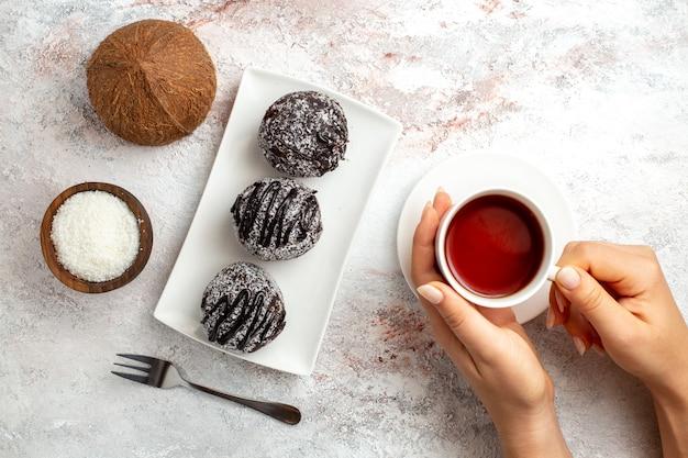 Bovenaanzicht chocoladetaarten met kopje thee en kokos op witte ondergrond chocoladetaart biscuit suiker zoete koekjes