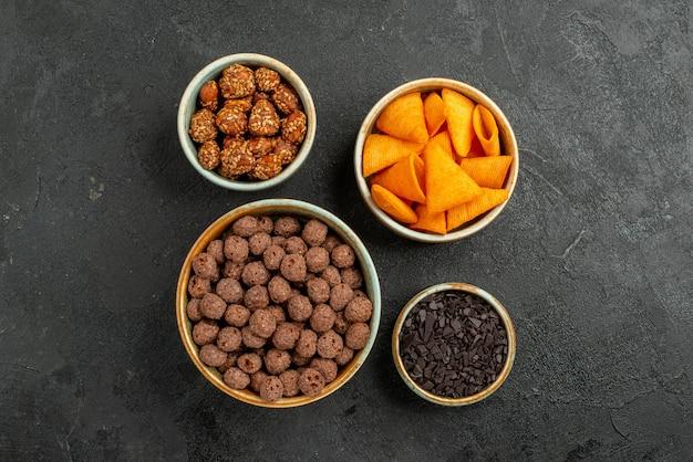 Bovenaanzicht chocoladevlokken met chips en noten op donkere achtergrond maïs kleuren noot