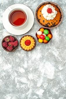 Bovenaanzicht chocolate chips cake met kopje thee op witte achtergrond zoete taart cookie biscuit cake suiker